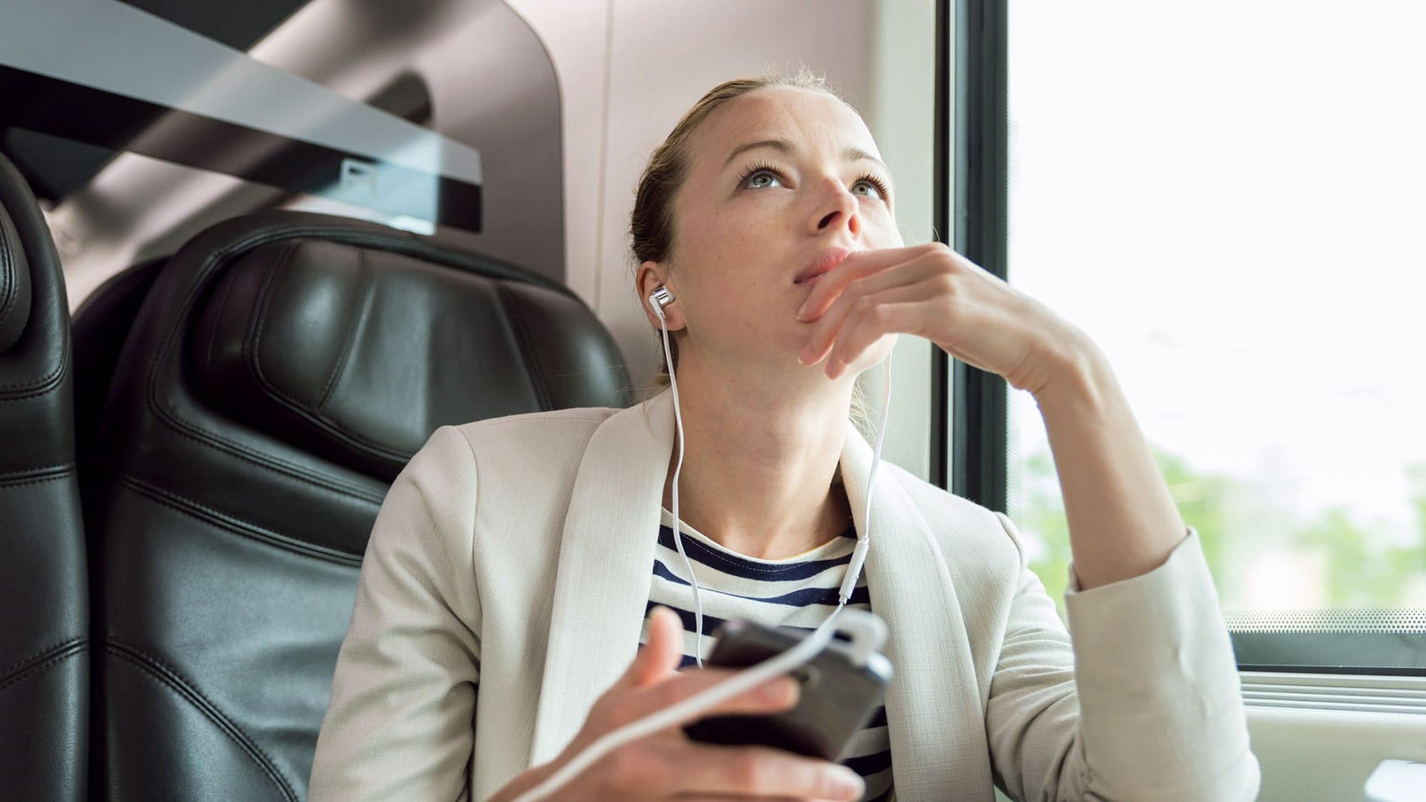 Eine Frau hört einen Podcast im Zug.